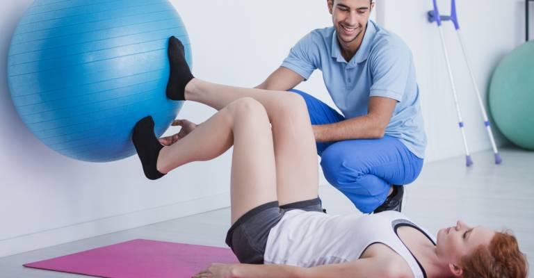 fysiotherapeut helpt vrouw met voeten bal tegen muur drukken